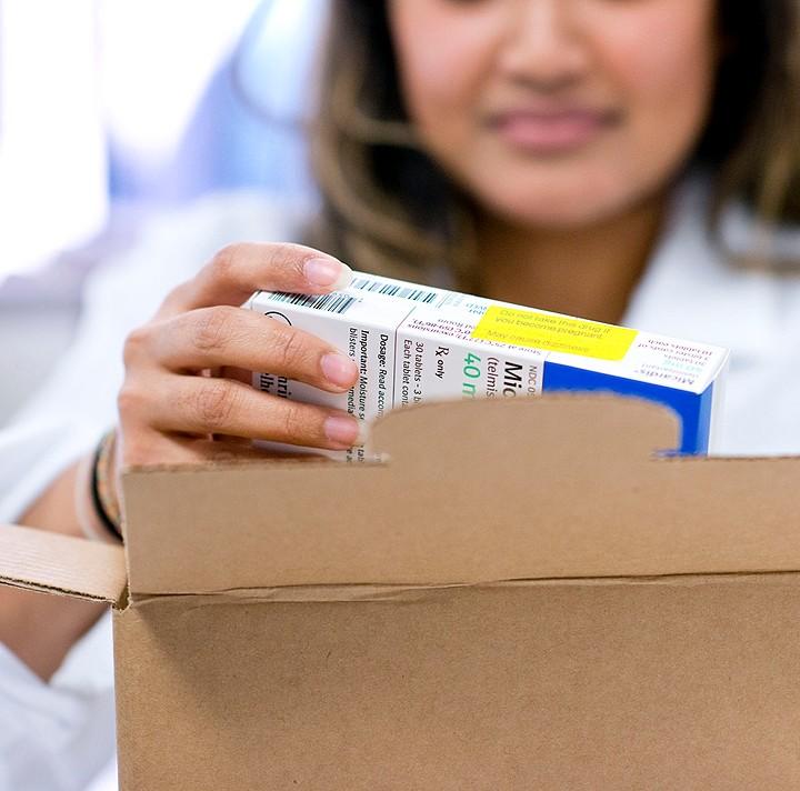 pharmacist putting meds in box