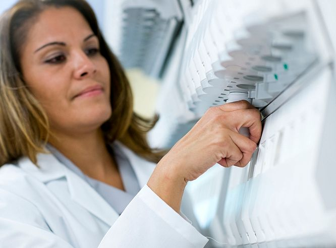 Woman pharmacist working on equipment